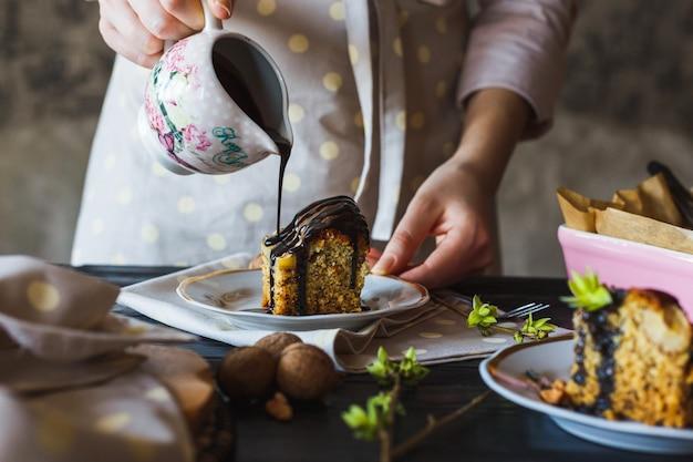 Torta di banane fatta in casa versando con cioccolato liquido caldo Foto Premium