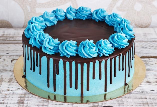 Torta di compleanno con gocce di cioccolato crema su uno sfondo bianco Foto Premium