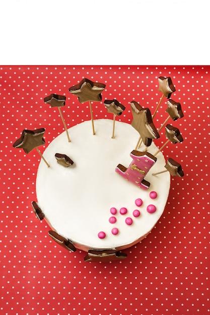 Torta di compleanno con pan di zenzero dorato a forma di stella e numero 1 su pois rosso Foto Premium