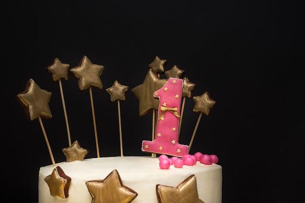 Torta di compleanno decorata con numero rosa 1 e stelle dorate di pan di zenzero. Foto Premium
