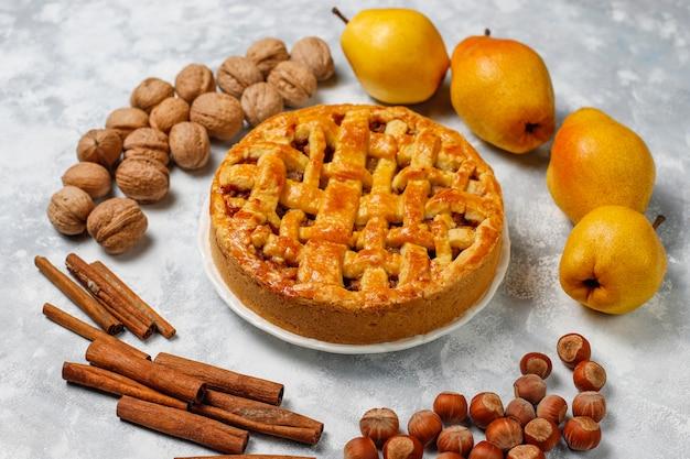 Torta di pere fatta in casa con cannella e noci su luce Foto Gratuite