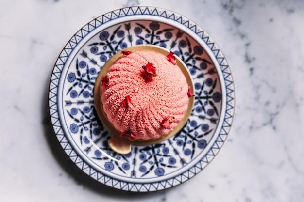 Torta di rose e litchi mousse decorata con petali di rosa in piatto di porcellana blu e bianca. Foto Premium
