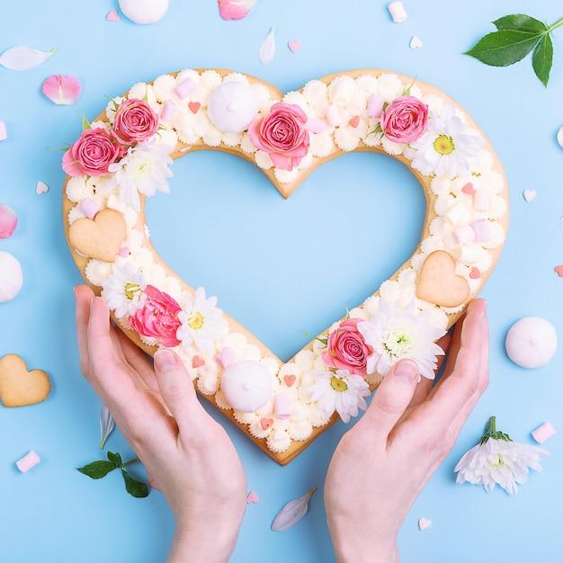 Torta di san valentino a forma di cuore con fiori come decorazione. Foto Premium