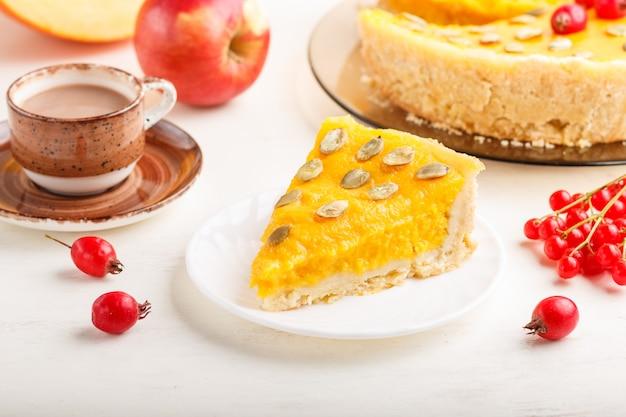 Torta di zucca dolce americana tradizionale decorata con bacche rosse e semi di zucca con una tazza di caffè su un fondo di legno bianco. Foto Premium