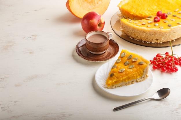 Torta di zucca dolce americana tradizionale decorata con le bacche e i semi di zucca rossi del biancospino con la tazza di caffè su un bianco di legno. vista laterale. Foto Premium