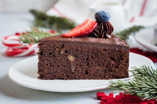 Torta natalizia per dessert. pezzo di dolce di cioccolato delizioso con la tazza di caffè e latte sulla tavola del calcestruzzo della pietra blu. concetto di cibo per la colazione. decorazione festiva Foto Premium