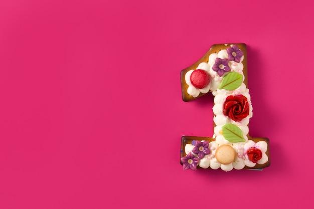 Torta numero uno decorata con fiori e biscotti sullo spazio di copia superficie rosa Foto Premium