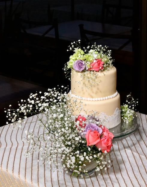 Torta nuziale con fiori sul tavolo | Scaricare foto gratis