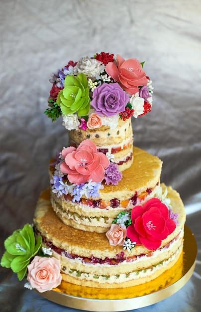 Torta nuziale. torta fatta a mano nuda rustica, decorata con rose. Foto Premium