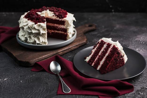 Torta rossa del velluto su priorità bassa scura, vista laterale del primo piano. dessert dolce per le vacanze. Foto Premium
