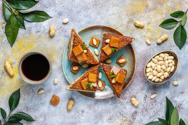 Torta squisita del caramello e dell'arachide con le arachidi e le caramelle del caramello, vista superiore Foto Gratuite