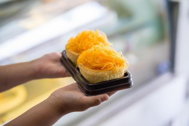 Torte di fili d'oro tuorlo d'uovo sulla mano del bambino, cibo dolce tailandese Foto Premium