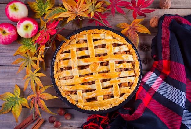 Torte di mele sul tavolo di legno con foglie di autunno e plaid Foto Premium