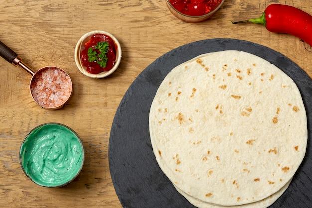 Tortilla vicino salse, sale rosa e pepe sul tavolo Foto Gratuite