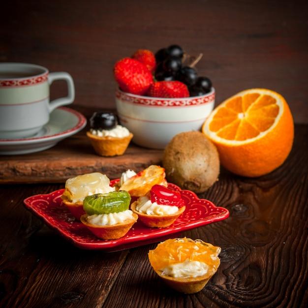 Tortine assortite con una tazza di tè e un piatto di frutta e arancia nel piatto Foto Gratuite