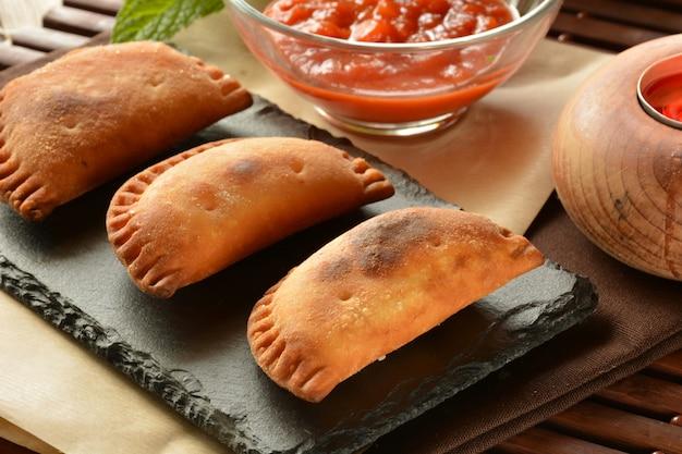 Tortino di tonno fatto in casa con salsa di pomodoro sul tavolo di legno Foto Premium