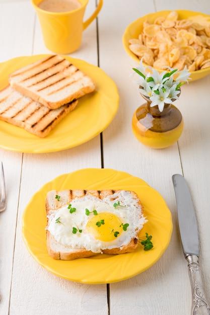 Tosti con l'uovo in piatto giallo vicino al vaso con il fiore su fondo di legno bianco. Foto Premium