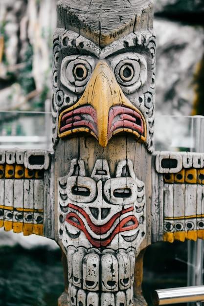 Totem indiano nazionale tradizionale. totem pole scultura art. maya e aztechi simbolici volti di divinità religiose. culto etnico pagano e idolatria. Foto Premium