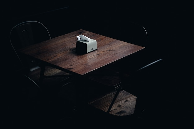Tovaglioli su un tavolo in una stanza buia Foto Gratuite