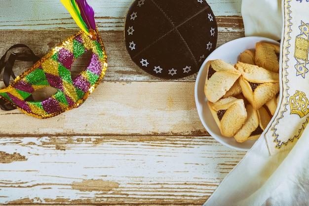 Tradizionale festa di carnevale ebraico purim celebrazione e biscotti e maschera hamantaschen, kippa Foto Premium