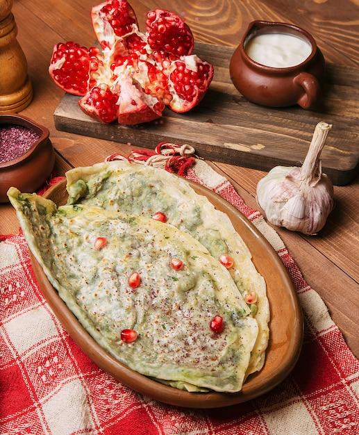 Tradizionale gutab vegetale caucasico, kutab, gozleme con sumakh, semi di granato e yogurt in piatto di legno Foto Gratuite