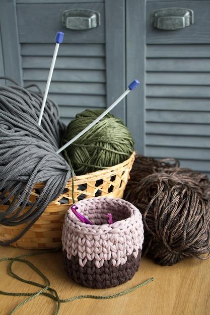 Tradizionali filati colorati per hobby a maglia in un cestino di paglia eco su una superficie di legno chiaro. Foto Premium