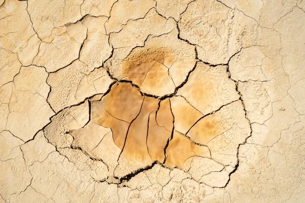Trama di argilla secca incrinata. conseguenze del riscaldamento globale. cambiamento climatico Foto Premium