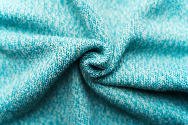 Trama stropicciata di un tessuto a maglia turchese blu. maglione sullo sfondo Foto Premium