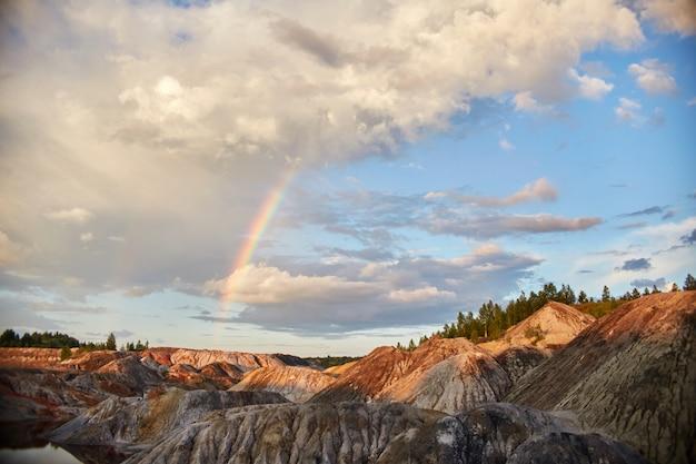 Tramonto con un arcobaleno nelle colline della sabbia. fiaba Foto Premium