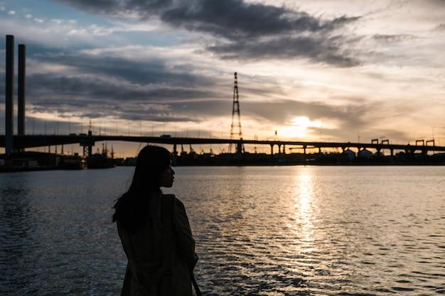 Tramonto della ragazza in mare e ponte Foto Gratuite
