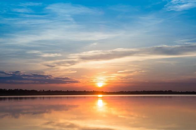 Tramonto nel lago. bel tramonto dietro le nuvole sopra lo sfondo del paesaggio del lago. Foto Premium