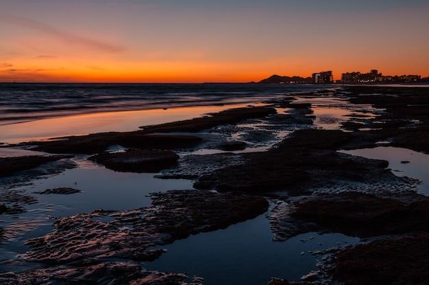 Tramonto su una spiaggia rocciosa di fronte all'hotel di puerto penasco in messico Foto Premium