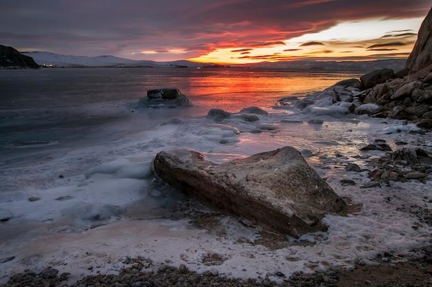 Tramonto sul lago baikal, tutto è coperto di neve ghiacciata Foto Premium