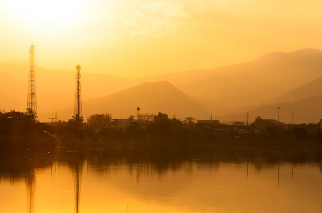 Tramonto sul lago in nebbioso con linee elettriche in background Foto Premium