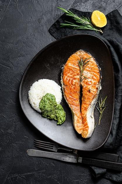 Trancio di salmone alla griglia guarnito con riso e spinaci. vista dall'alto Foto Premium