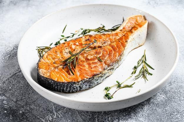 Trancio di salmone arrosto. frutti di mare sani. sfondo grigio. vista dall'alto Foto Premium