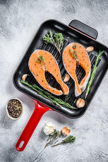 Trancio di salmone con rosmarino e pepe in padella. pesce biologico crudo spazio grigio. vista dall'alto Foto Premium