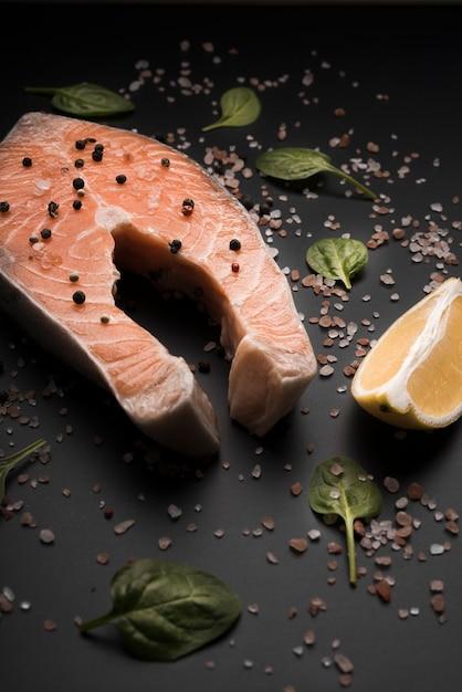 Trancio di salmone crudo ad alto angolo con pepe e limone Foto Gratuite