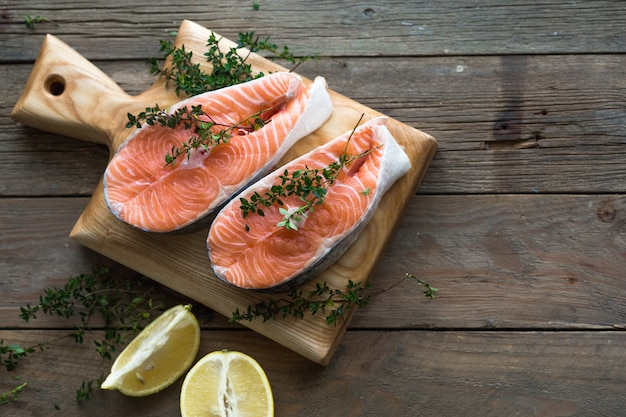 Trancio di salmone crudo e fresco su una tavola di legno e spezie intorno. pesce rosso salmone crudo. cucinare salmone, frutti di mare. concetto di cibo sano. salmone e spezie Foto Premium