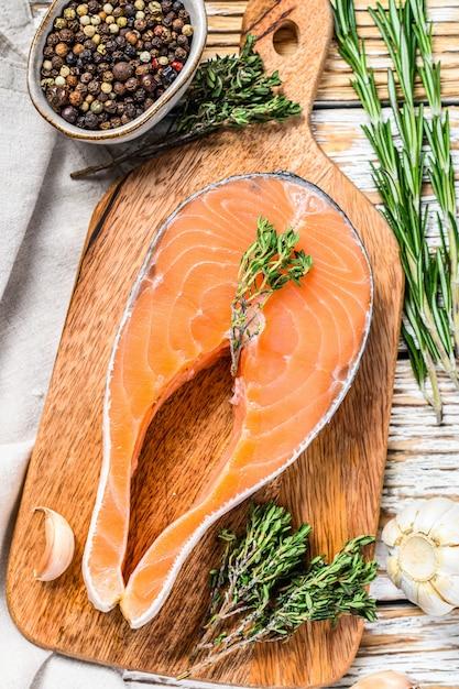 Trancio di salmone crudo fresco con pepe e timo. spazio in legno bianco. vista dall'alto Foto Premium