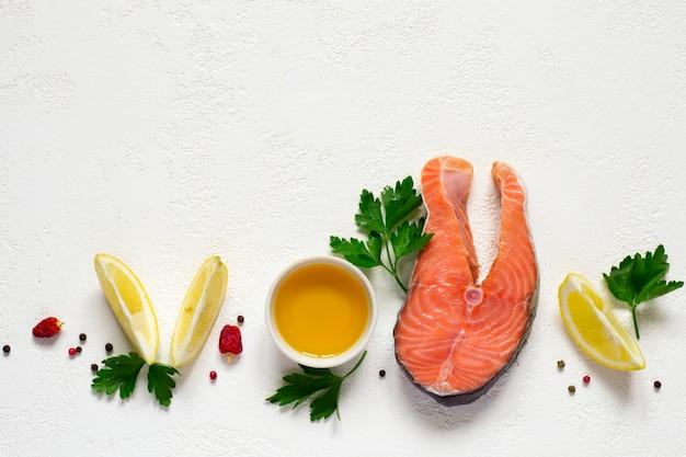 Trancio di salmone crudo fresco, olio d'oliva, limone e spezie Foto Premium