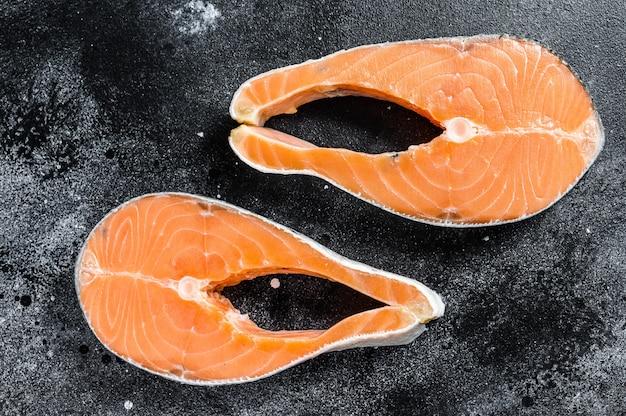 Trancio di salmone crudo, pesce biologico. spazio nero. vista dall'alto Foto Premium