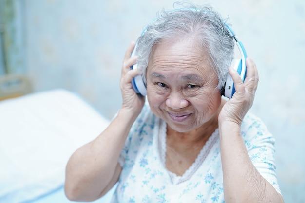 Trasduttore auricolare paziente asiatico di uso della donna senior mentre sedendosi sul letto in ospedale. Foto Premium