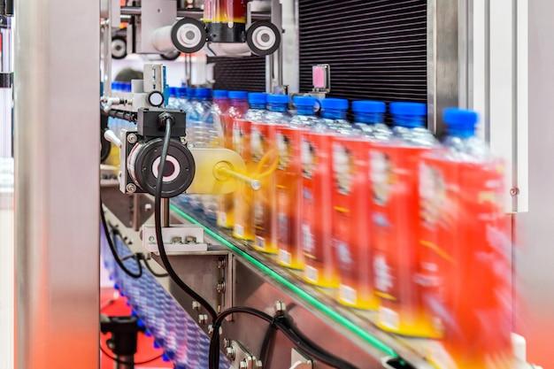 Trasferimento chiaro di bottiglie su automazione industriale di sistemi di trasporto automatizzati per pacchetto Foto Premium