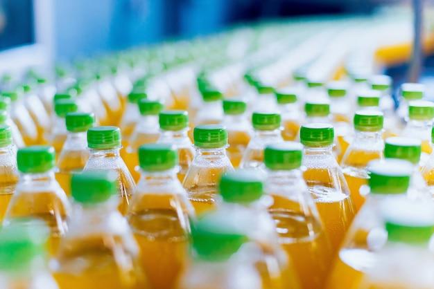 Trasportatore con bottiglie per succo o acqua. attrezzature per fabbriche di bevande Foto Premium