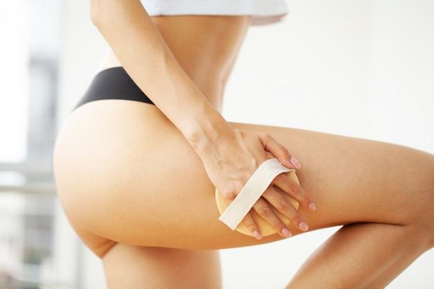 Trattamento anticellulite, braccio donna con pennello asciutto sulla parte superiore della gamba Foto Premium