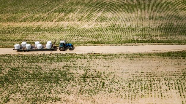 Trattore cavalca sul campo e trasporta balle di fieno vista aerea Foto Premium
