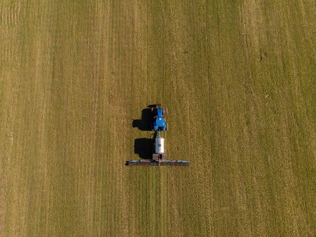 Trattore che applica fertilizzanti minerali liquidi al suolo sul frumento autunnale Foto Premium