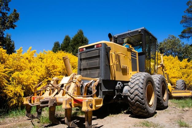 Trattore giallo su terreno agricolo. Foto Premium