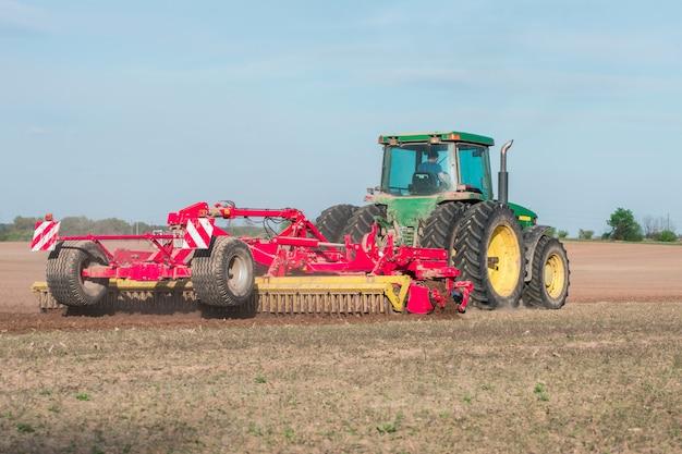 Trattore in un campo che ara terra Foto Premium